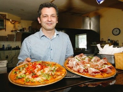 Owner Nader Hatami hold's two of his Pizzas from the Steveston Pizza Company